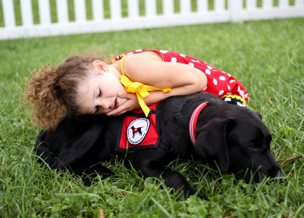 Photo of an autistic child and an autism assistance dog