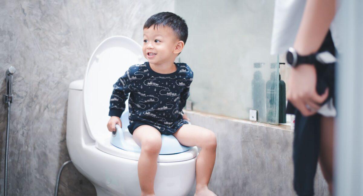 Boy sitting on toilet bowl