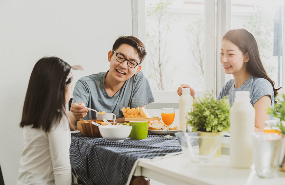 Man, woman and girl having a meal at a table